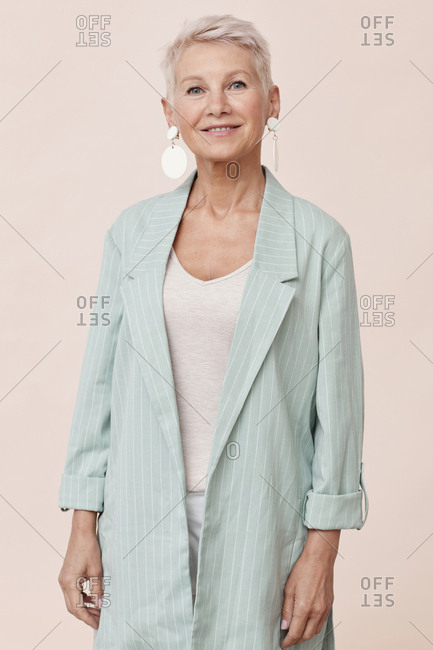 Caucasian woman with short blond hair wearing stylish blazer looking at camera smiling