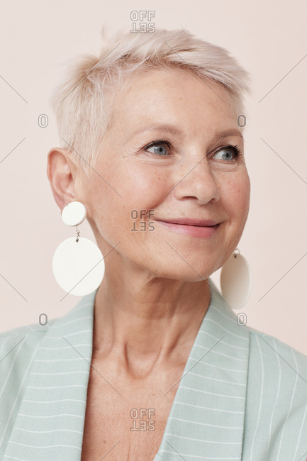 Positive middle-aged woman with short blond hair wearing stylish earrings looking away portrait