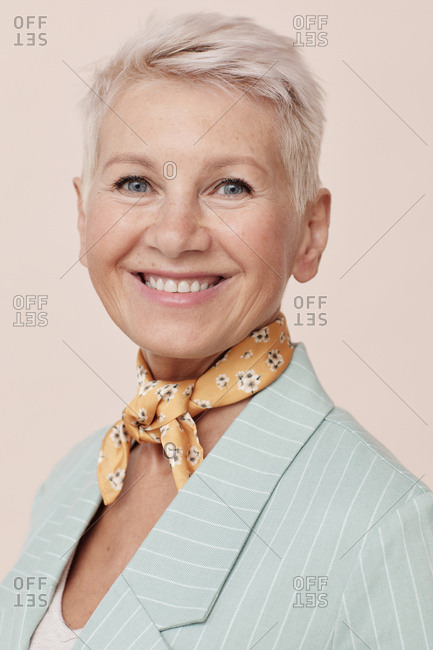 Elegant mature model wearing small silk scarf around her neck looking at camera portrait