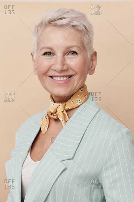 Elegant mature woman wearing small yellow silk neck scarf looking at camera smiling portrait