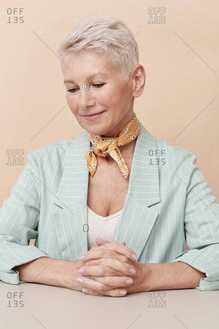 Attractive mature businesswoman wearing small yellow silk neck scarf sitting at office desk