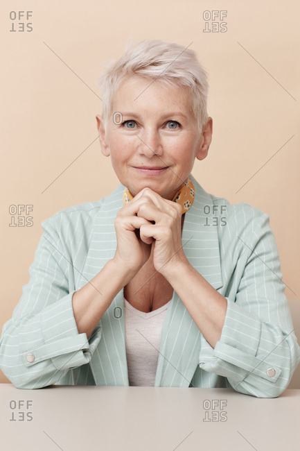 Caucasian mature businesswoman sitting at office desk with hands folded looking at camera