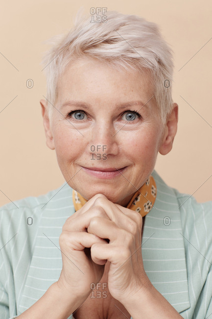 Caucasian middle-aged woman with hands folded looking at camera close up portrait