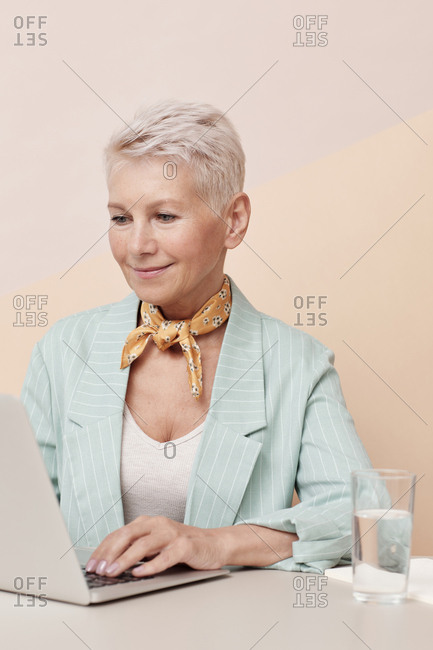 Caucasian mature woman working on laptop sitting at desk against beige wall background