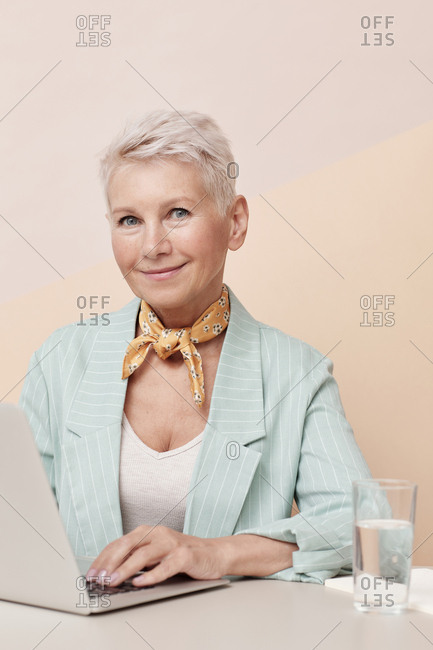 Caucasian mature woman looking at camera while working on laptop sitting at office desk