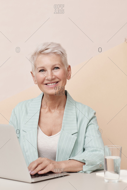 Caucasian mature woman smiling at camera while working on laptop sitting at office desk