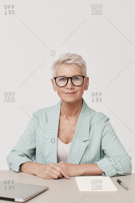 Stylish mature woman wearing eyeglasses sitting at office desk looking at camera