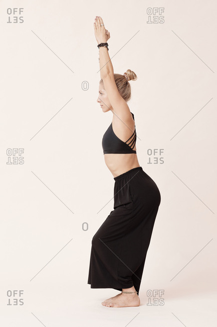 Young woman wearing black outfit practicing chair pose asana, side view shot