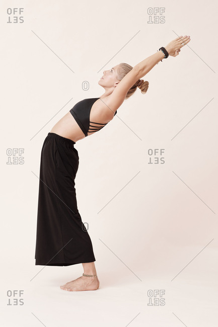 Young woman wearing black outfit practicing yoga against beige background, side view shot