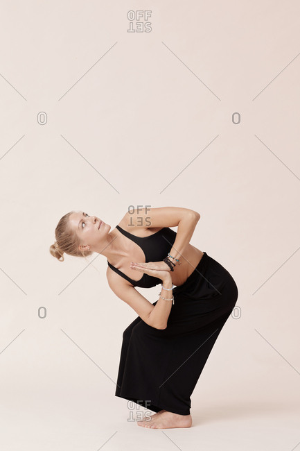 Caucasian woman in black practicing revolved chair pose asana against beige background