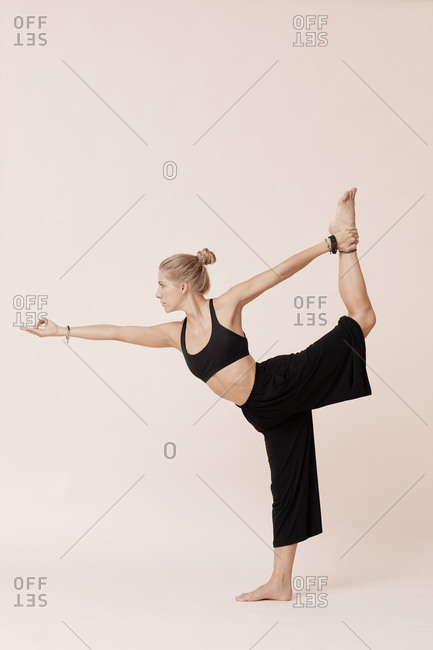 Beautiful young woman practicing lord of dance yoga pose against beige background studio shot