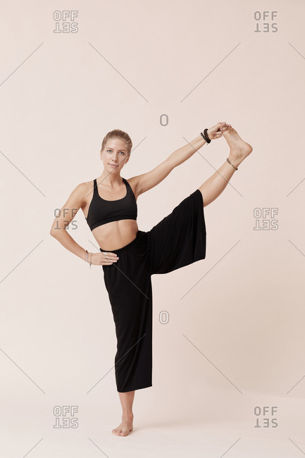 Attractive young woman in black practicing extended hand-to-big-toe pose against beige background studio shot