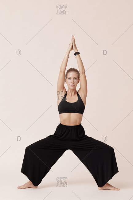 Attractive young woman in black doing yoga exercises against beige background studio shot