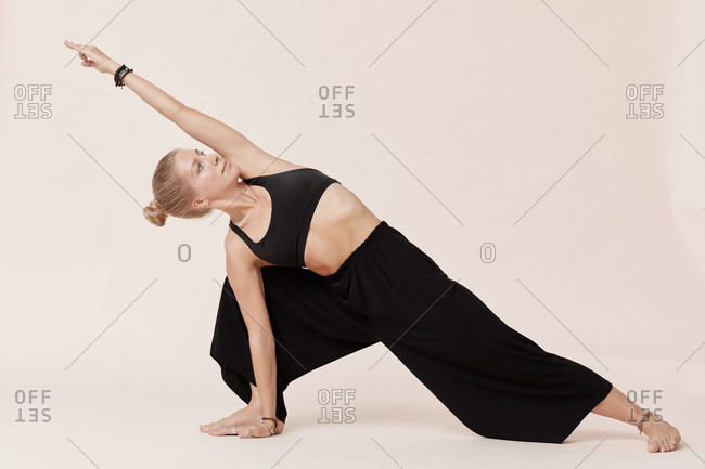 Beautiful young woman in black outfit practicing side angle yoga pose studio shot