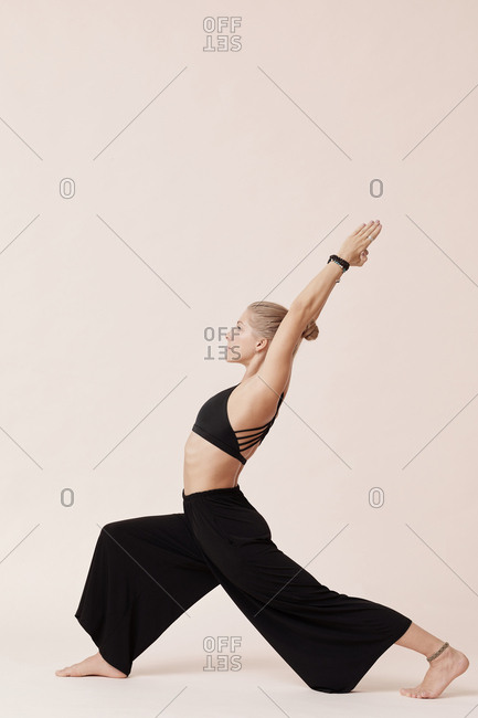 Good-looking young woman wearing black outfit practicing high lunge asana studio shot