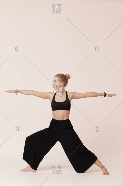 Young woman wearing stylish black clothes practicing warrior pose side view shot