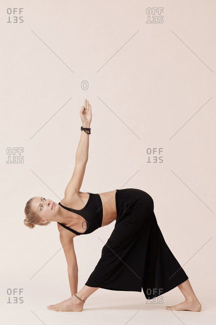 Young woman in black clothes practicing revolved triangle pose asana studio shot