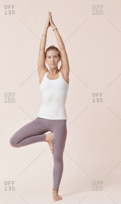 Caucasian girl practicing tree pose against beige background