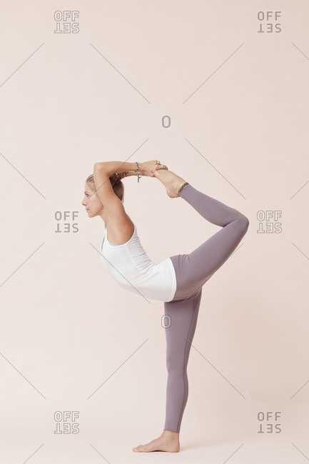 Beautiful young woman practicing full lord of dance yoga pose against beige background studio shot