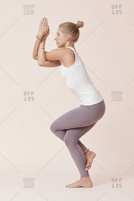 Sporty young woman practicing eagle yoga pose side view studio shot
