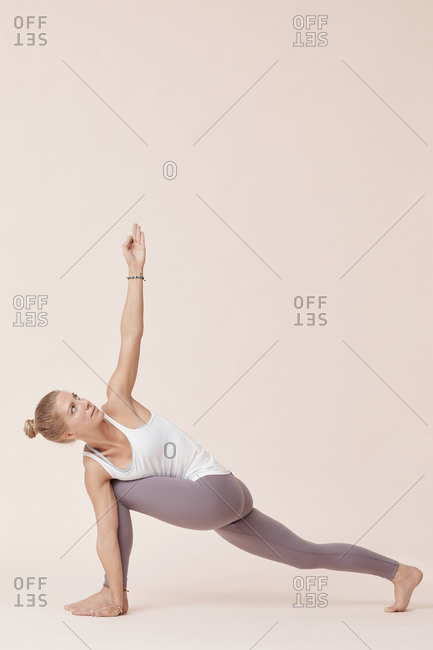 Caucasian woman practicing extended side angle yoga pose studio shot