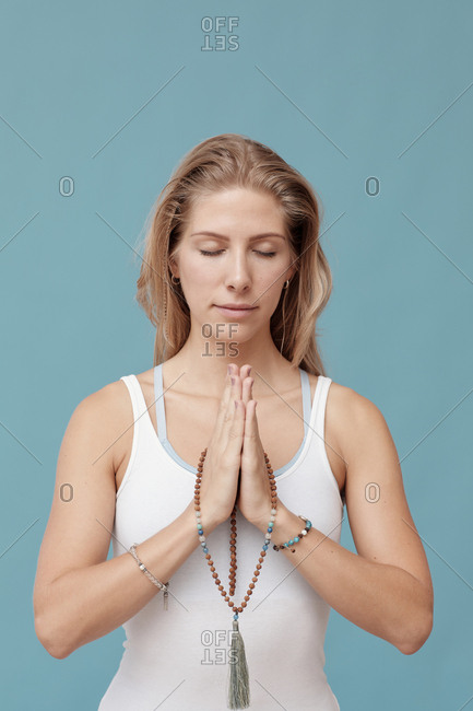 Caucasian woman meditating with praying hands and eyes closed vertical waist up portrait