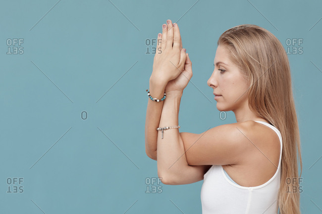 Attractive young woman practicing yoga twisted arms exercise side view shot, blue background