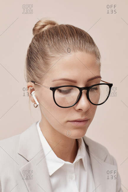 Young female office worker listening to music using modern wireless earphones
