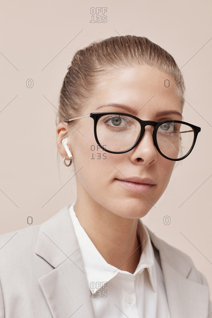 Young businesswoman wearing stylish eyeglasses and wireless earphones looking at camera