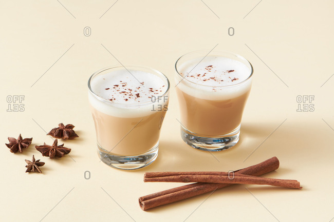 Tea latte with cinnamon and anise on solid color background