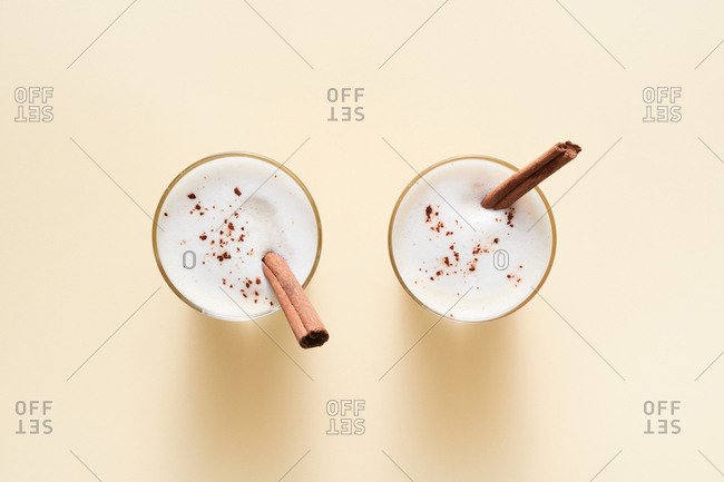 Tea latte with cinnamon and anise on solid color background -  from above