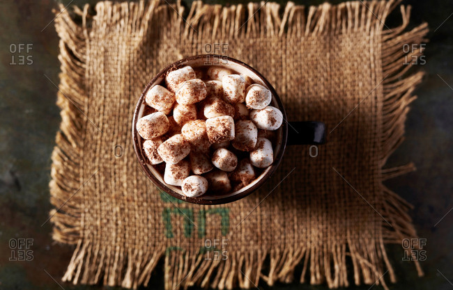 Hot chocolate with lots of marshmallows and chocolate shavings in rustic setting