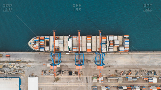 April 8, 2019: Aerial view of beautifully abstract container ship being loaded at Malaga Port, Spain