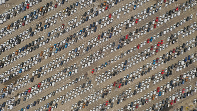 Aerial view of colorful cars abstractly parked ready to sell in Malaga Port, Spain