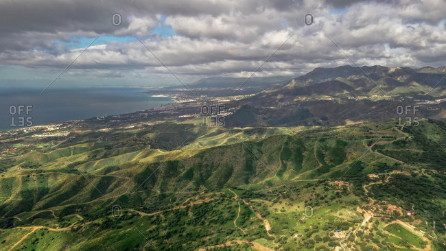 Aerial view of wonderful coast colorful mountains with heavy clouds before a storm in Marbella, Spain