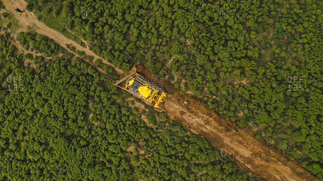 April 9, 2019: Aerial view of yellow machine deforesting beautiful trees in mountains of Marbella, Spain
