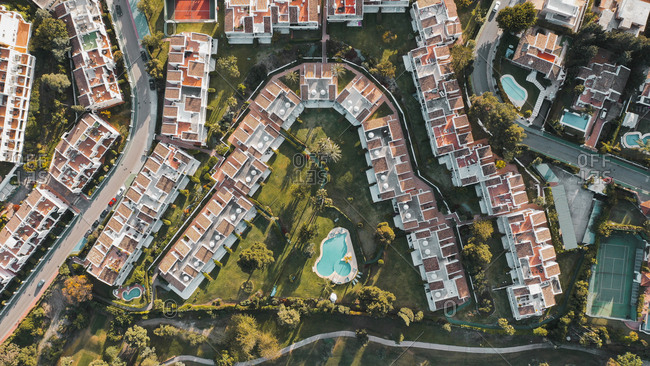 Aerial view of colorful houses beautifully arranged next to a wonderful golf course in Marbella, Spain
