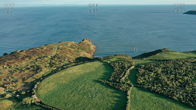 Aerial view of beautiful coast and blue ocean with green fields in Nicholaston, Wales