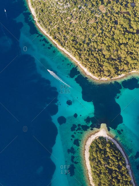 Aerial view of boat sailing at strait between Koludarc island, Croatia.