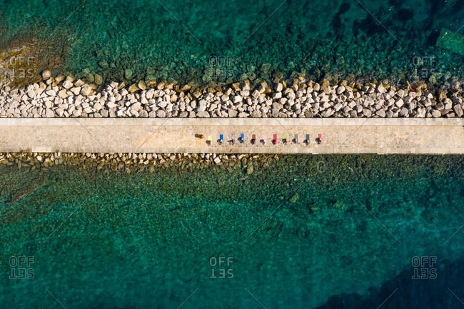 Aerial view of group practicing yoga at artificial pier, Veli Losinj, Croatia.