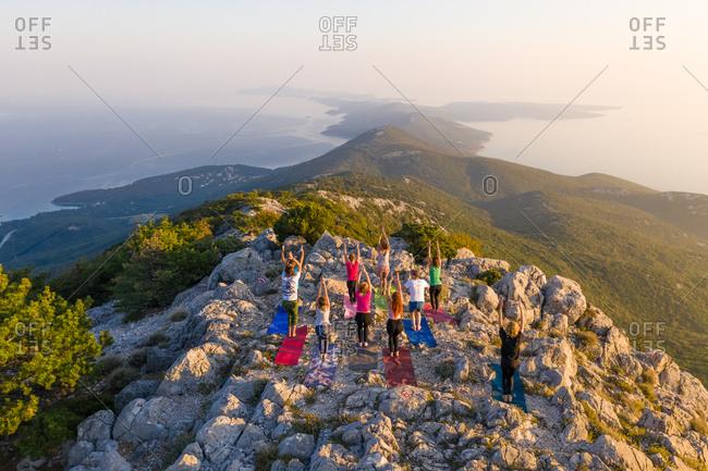 October 13, 2018: Aerial view of group practicing yoga at top of mountain, Veli Losinj, Croatia.