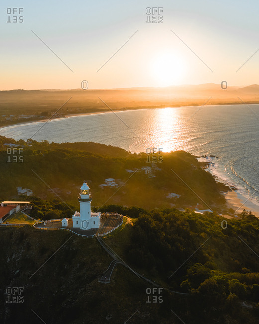 Aerial view of Byron Bay lighthouse at sunset in Australia.