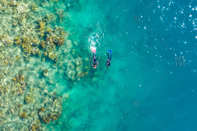 Aerial view of two persons snorkeling at Great Barrier Reef in Australia.
