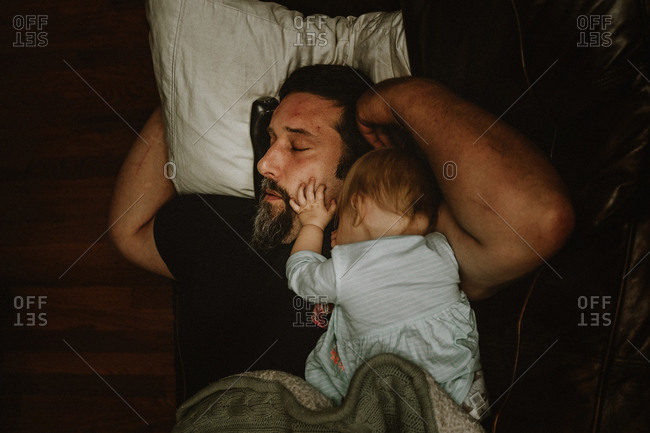 Overhead view of a father napping with a baby