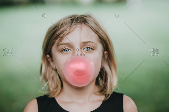 Little blonde girl blowing a bubble with her gum