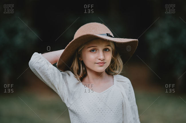 Portrait of a blonde girl wearing a large hat