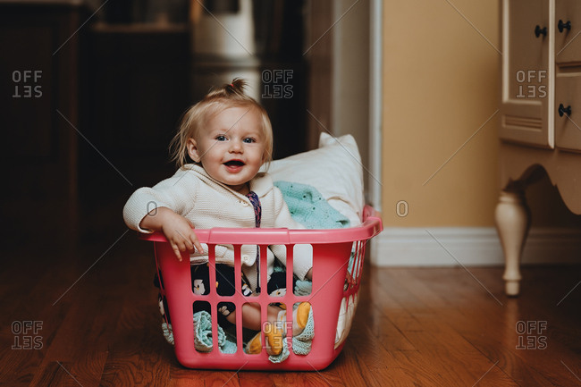 Blonde baby sitting in laundry basket