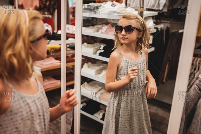 Girl trying on sunglasses in a store