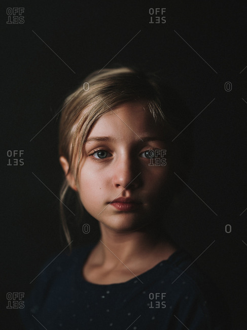 Portrait of a pretty little blonde girl with blue eyes on dark background