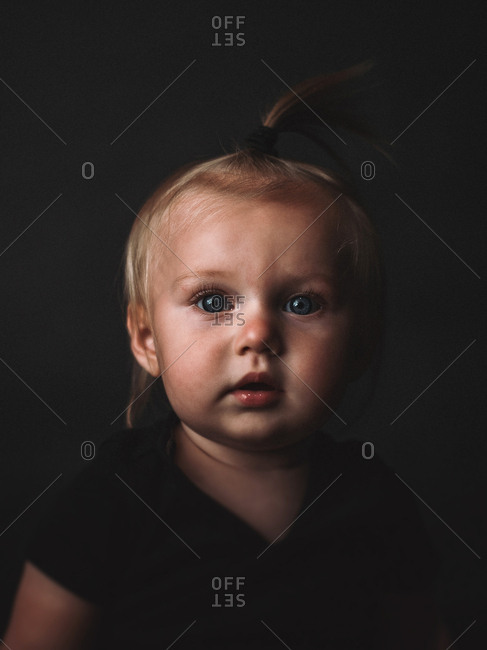 Portrait of a cute blonde baby with blue eyes on dark background